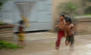 Des enfants sous la pluie à Dacca, au Bangladesh, le 28 avril 2010