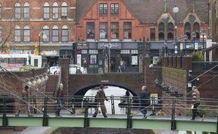 Des passants traversent un pont sur un canal à Birmingham, dans le centre de l'Angleterre, le 14 mars 2015