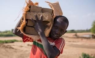 Un enfant transportant des briques au Soudan du Sud.