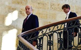 Alain Juppé, suivi par son adjoint aux finances Nicolas Florian descend le grand escalier de l'hôtel de ville.