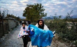 Un homme porte son enfant alors qu'il vient avec d'autres migrants de passer la frontière gréco-macédonienne près de Gevgelija, en Macédoine, le 15 novembre 2015