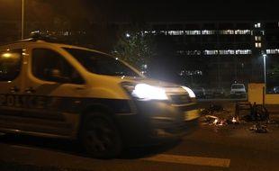 Une voiture de police passe près d'une poubelle incendiée à Villeneuve-la-Garenne, le 20 avril 2020.