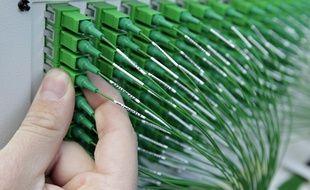 Illustration d'un technicien intervenant sur une armoire de raccordement à la fibre optique.