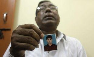Le père de Quazi Mohammad Rezwanul Ahsan Nafis tient une photo de son fils, accusé d'avoir préparé un attentat terroriste à New York, le 18 octobre 2012, à Dacca (Bangladesh).