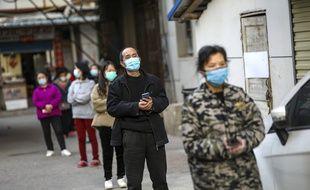 Des habitants de Wuhan en attente de se ravitailler en nourriture le 18 mars 2020.