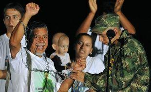 Le sergent colombien Pablo Emilio Moncayo (D) qui vient d'être libéré par les Farc, retire les chaînes que son père Gustavo Moncayo porte symboliquement depuis plusieurs années, à l'aéroport de Florencia le 30 mars 2010.