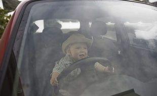 Un enfant joue dans une voiture. (illustration)