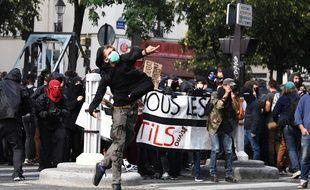 Un jeune homme lance un projectile lors de la manifestation contre la réforme du Code du travail, mardi 12 septembre à Paris.