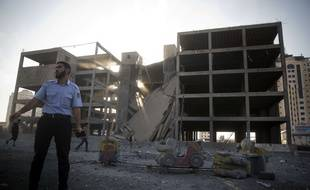 Un policier palestinien se tient à côté ds ruines d'un bâtiment détruit par un raid israélien le 14 juillet 2018.