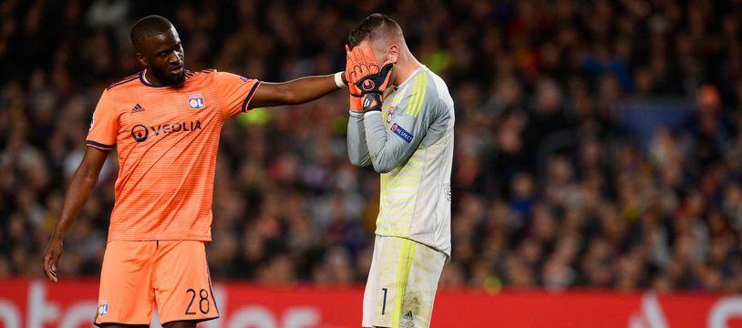 Tanguy Ndombele tente de consoler Anthony Lopes, dépité de devoir quitter le terrain après seulement 34 minutes de jeu, mercredi au Camp Nou. Josep LAGO