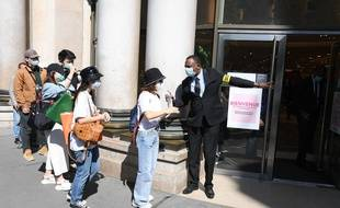 Un vigile à l'entrée d'un grand magasin parisien vérifie que les clients portent un masque et se nettoient les mains au gel hydroalcoolique avant d'entrer.