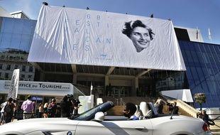 La bâche en train d'être hissée, sur le fronton du Palais des festivals de Cannes, le 11 mai 2015.