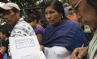 """Une Mexicaine exhibe le contrat que les parents signaient en confiant la garde de leurs enfants au foyer """"La Gran Familia""""(la grande famille) où la police a fait un raid et libéré 596 personnes dont 458 enfants à Zamora, au Mexique le 16 juillet 2014"""
