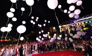 Les familles des victimes lancent des ballons lors du concert en hommage à leurs proches décédés.