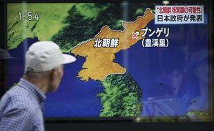 Un passant devant une  télévision et une carte montrant le lieu de l'explosion d'un essai nucléaire nord-coréen, le 3 septembre 2017 à Tokyo au Japon