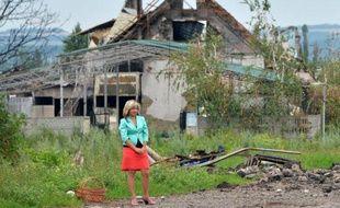 Tout près de Slaviansk, ex-bastion des insurgés pro-russes, dans le village de Semyonovka en Ukraine, une femme attend une voiture devant une maison détruite par les combats, le 9 juillet 2014