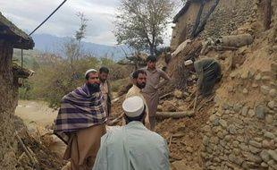 Des pakistanais se rassemblent près des décombres de plusieurs maisons, après un puissant séisme à Bajaur, au Pakistan, le 26 octobre 2015
