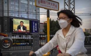 Une femme passe devant un écran diffusant un discours du président chinois Xi Jinping, le 30 juin 2020 à Pékin.