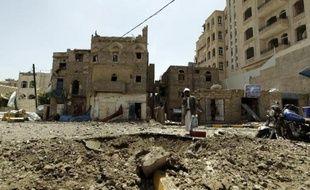 Un homme au milieu des ruines après un bombardement le 20 avril 2015 à Attan, une colline surplombant le sud de Sanaa