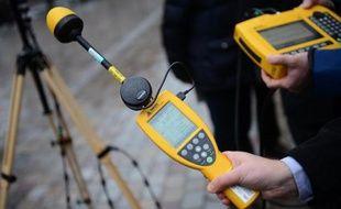 Des techniciens mesurent les émissions électromagnétiques dans une rue de Paris, en janvier 2013