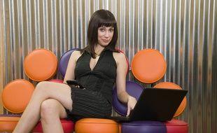 Une jeune femme assise sur un canapé, devant un ordinateur portable.