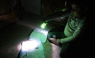 Pénurie: Un petit garçon utilise une lampe électrique pour faire ses devoirs durant une coupure de courant à Bagdad le 19 mars 2014