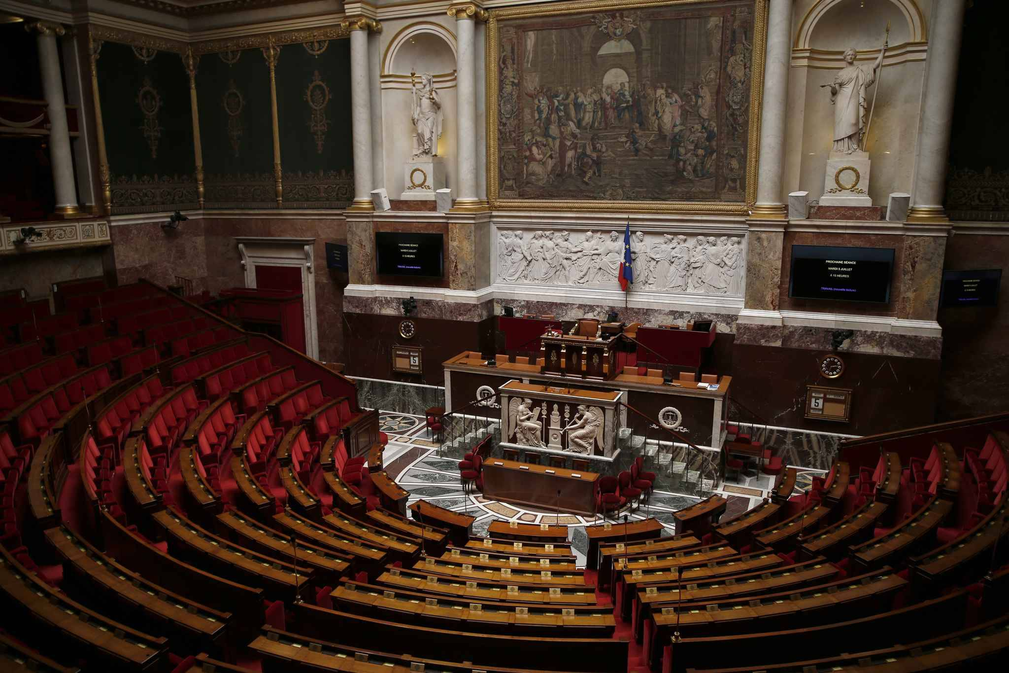 The empty assembly room of the French National Assembly is pictured prior to a debate on the government's planned labour law reforms on July 5, 2016 in Paris.  The French Socialist government was reportedly poised on July 5, 2016 to push through labour reforms without a vote as protesters gathered for their 12th show of opposition to the controversial package since March.