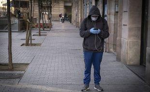 Un utilisateur masqué de smartphone à Barcelone, au temps de Covid-19.
