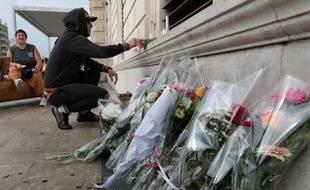Des passants déposent des fleurs et allument des bougies, gare Saint-Charles.