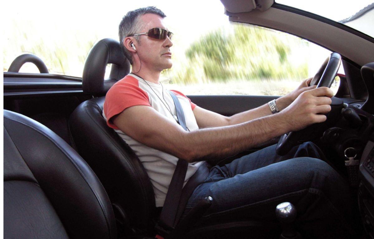 Un homme conduit avec un kit mains libres. – Jaubert / Sipa