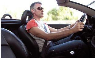 Un homme conduit avec un kit mains libres.