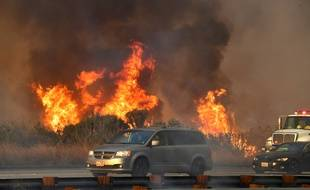 Les automobilistes conduisent cernés par des incendies sur la route US 101 menant à la plage de Faria, au nord de Ventura, en Californie, le 7 décembre 2017.