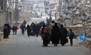 Alep (Syrie), le 12 décembre 2016. Des civils fuient le quartier de Soukkari que l'armée de Bachar al-Assad vient de reprendre aux rebelles.