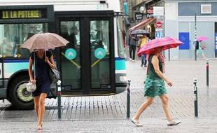Deux femmes marchent sous la pluie à Rennes, en été (illustration).