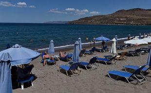 Des touristes prennent le soleil sur la terrasse d'un hôtel près du village de Molyvos, sur l'île de Lesbos, le 20 juillet 2016