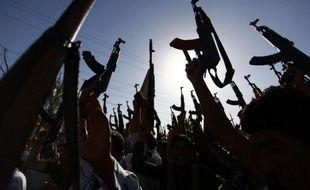 Des Irakiens chiites brandissent leurs armes pour montrer leur volonté de rejoindre les combats anti-jihadistes, le 17 juin 2014 à Najaf au sud de l'Irak