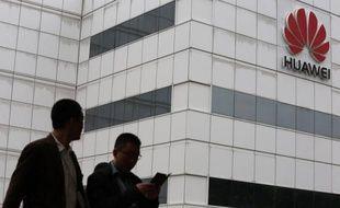 """People walk by a building on the Huawei campus L'équipementier chinois en télécommunications Huawei a annoncé lundi une hausse de 32% de son bénéfice net et espère """"résoudre les défis et les problèmes"""" qu'il rencontre aux Etats-Unis qui lui reprochent ses liens avec les autorités chinoises."""