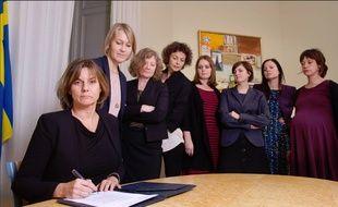 Isabella Lövin signe le projet de loi sur l'environnement suédois entourée de ses collègues féminines.
