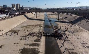 Un groupe de migrants d'Amérique centrale traverse le lit de la rivière Tijuana afin de se rendre à Tijuana, près de la frontière américano-mexicaine, le 25 novembre 2018.