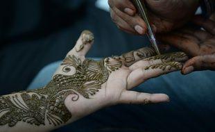 Une jeune fille indienne se fait tatouer la main au henné pour fêter l'Aïd el-Fitr, la fin du ramadan, à Bombay le 6 juillet 2016