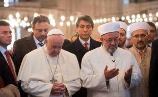 Le pape François (g) se recueille dans la Mosquée bleue d'Istanbul aux côtés du grand mufti Rahmi Yaran, le 29 novembre 2014