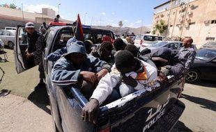 Des migrants d'Afrique subsaharienne sont emmenés dans un centre à Tripoli, après avoir été arrêtés, le 17 mai 2015