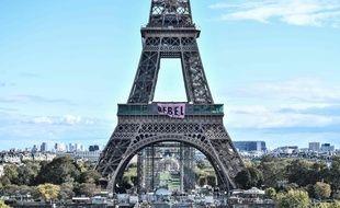 """Des militants du mouvement écologiste Extinction Rébellion (XR) ont déployé dimanche une banderole avec l'inscription """"Rebel"""" (""""rebellez-vous"""" ou """"rebelle"""") au premier étage de la tour Eiffel à Paris."""