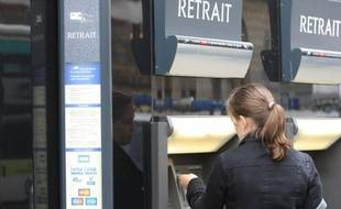 Une femme retire de l'argent à Paris le 24 janvier 2008
