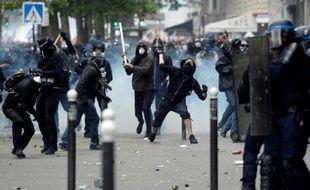 Des personnes cagoulées face à des policiers lors de la manifestation contre la loi travail à Paris, le 14 juin 2016