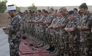 Une photo distribuée par le Palais royal du roi Abdallah II qui prie avec des soldats dans un endroit non défini en Jordanie, le 20 juin 2016