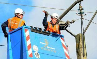 Des agents ERDF réparent une ligne électrique sur un pilône après le passage de la tempête Dirk, le 26 décembre 2013 (illustration