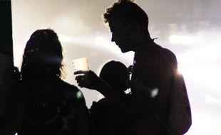 Un homme et une femme partagent un verre de bière devant une scène du festival des Vieilles Charrues, en 2015.