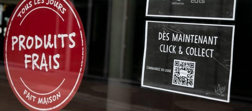 Affichage d'un Click & collect et d'une livraison à domicile sur la façade d'un restaurant de La Défense, à Paris.