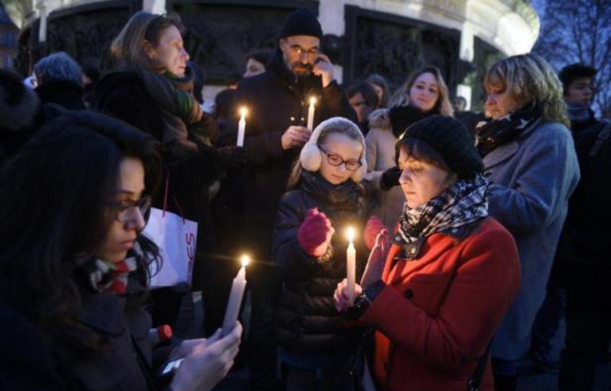Des personnes lors du rassemblement en hommage aux victimes de l'attaque du journal Charlie Hebdo qui a fait 12 morts, le 7 janvier 2015 à Paris – Martin Bureau AFP